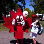 Maple leaf mascot accepting new toothbrush from dental staff